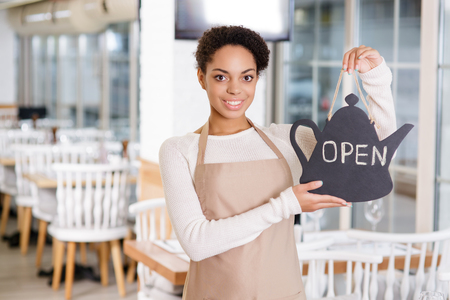 upholding: We are open. Attractive young waitress is smiling while upholding an opening sign for the restaurant.