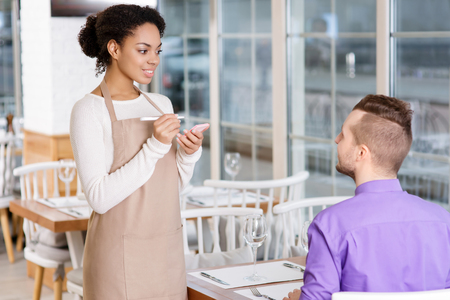 pleasing: Serving a client. Pleasing young waitress is busy taking order. Stock Photo