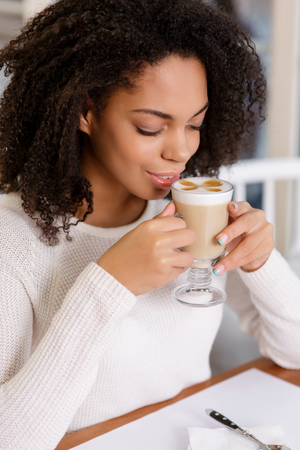 appreciating: Appreciating the drink. Young beautiful woman enjoying her cup of latte.