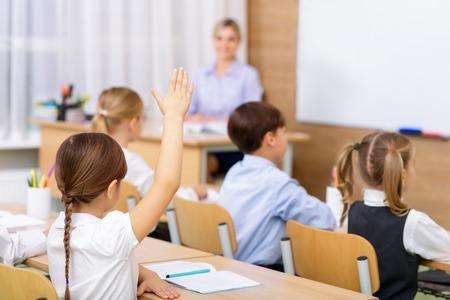 좋은 학생. 작은 학생이 교사의 질문에 대한 답을 알고 있음을 나타내는 공중에서 그녀의 손을 들어 올리고 있습니다.