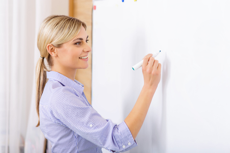 Writing on whiteboard. Attractive female teacher is busy writing on the whiteboard during the lesson.