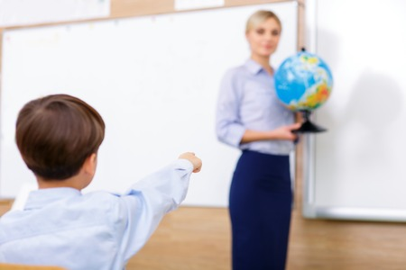 school age boy: Nice globe. Little boy looks interested in globe model which is carried by the teacher. Stock Photo