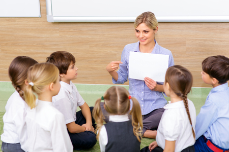 successfully: Interesting lesson. Young female teacher successfully communicating with her pupils by discussing a picture. Stock Photo