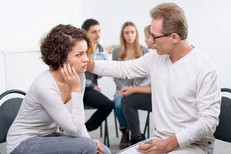 Klaar om een stuk van advies te geven. Geconcentreerde professionele psycholoog te praten met zijn patiënt met een groep mensen praten op de achtergrond tijdens de psychologische groepstherapiezitting