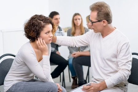 advice: Ready to give a piece of advice.  Concentrated professional psychologist talking with his patient with group of people talking in the background during psychological group  therapy session