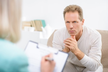 complain: What do you complain about. Close up of upset serious man sitting on the couch and feeling cheerless while speaking with psychologist. Stock Photo