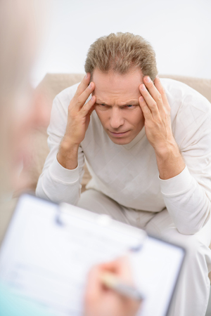 revel: Revel you problem. Upset senior man sitting on the couch and holding his head while talking with psychologist during psychological therapy session Stock Photo