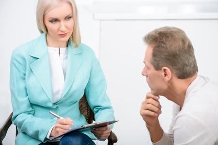 paciente: Te ayudaré. psicólogo profesional agradable que sostiene la carpeta y habla con el paciente durante la sesión de terapia psicológica