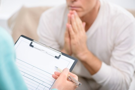 Tell me about your problem. Close up of folder in hands of professional psychologist holding it and interrogating her patient during psychological therapy session Reklamní fotografie - 48725106