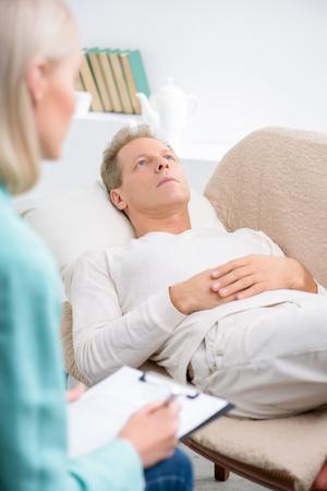 terapia psicologica: Relájate. Melancolía hombre mayor pensativa tumbado en el sofá y hablando con su psicólogo durante la sesión de terapia psicológica