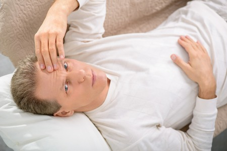 cheerless: Painful moment. Top view of gloomy cheerless senior man holding his head and lying on the sofa during psychological therapy session Stock Photo