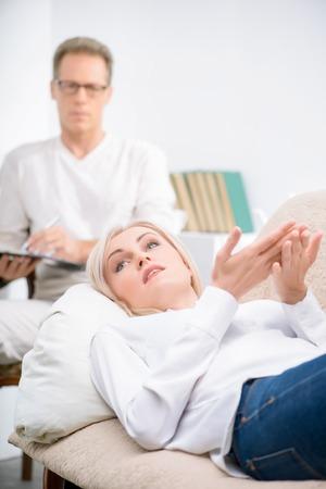 terapia psicologica: Descansar de problemas. Mujer agradable que miente en el sofá y hablar con el psicólogo durante la sesión de terapia psicológica