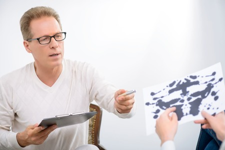 test paper: What does it mean. Pleasant professional psychologist giving test paper to his patient and testing her  during psychological therapy session