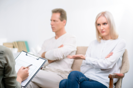 interrogating: Can not live together. Selective focus of folder in hands of professional psychologist holding it and interrogating adult couple sitting on the sofa in the background