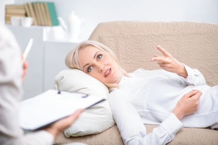 talkative: Want to share my problems. Nice talkative senior woman lying on the sofa and talking with  psychologist during psychological therapy session Stock Photo
