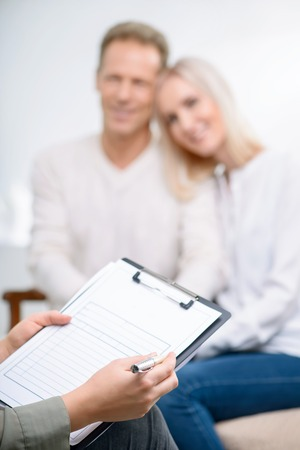 interrogating: Best professional. Selective focus of folder in hands of psychologist holding it and interrogating happy couple sitting in the background during psychological therapy session Stock Photo