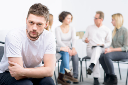cheerless: Out of mood. Depressed cheerless boy sitting in the chair with professional psychologist working in the background with people during psychological group  therapy session