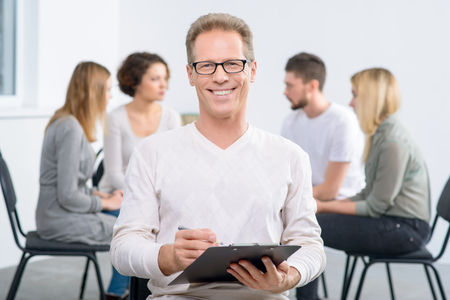 therapy group: Delighted with results. Content smiling  handsome professional psychologist holding folder and  smiling  with his group sitting in the background