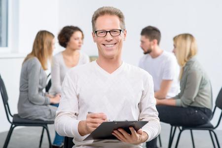 terapia grupal: Encantados con los resultados. Contenido hermoso sonriente que sostiene la carpeta profesional de la psicología y la sonrisa con su grupo sentado en el fondo