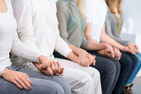 men women: Just relax. Close up of people sitting in  row  and holding hands of each other during psychological group  therapy session