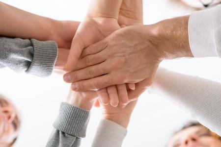 terapia psicologica: Est�n unidos. Bajo el �ngulo de las manos de la gente los sostiene uno sobre otro durante la sesi�n de terapia de grupo psicol�gica
