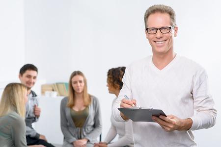terapia psicologica: Me encanta mi trabajo. contenido agradable y guapo psic�logo profesional que sostiene la carpeta con el paciente sentado en el fondo durante la sesi�n de terapia psicol�gica grupal