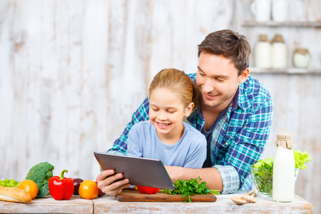glad: Have a look. Pleasant smiling glad father and daughter holding laptop and expressing gladness while going to cook Stock Photo