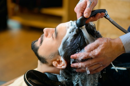 barbery: Just relax. Close up of pleasant professional hairdresser washing hair of his client while going to make haircut