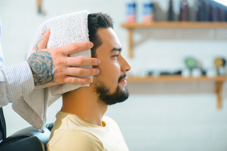 barbery: Almost ready. Close up of pleasant content man sitting in the barber shop with professional barber drying his hair Stock Photo