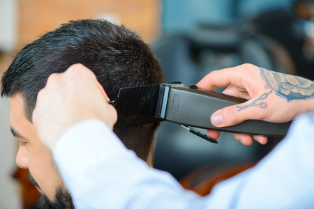 haircut: Best haircut. Close up of razor in hands of professional barber holding it and making haircut to his client