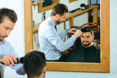 barbery: Happy client. Happy handsome man sitting in barber shop and looking in  a mirror while barber making him a haircut