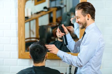 barbery: Best worker. Pleasant smiling professional barber using hairspray while making hairstyle to his client