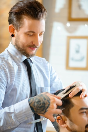 barbery: Best professional. Pleasant positive barber holding scissors and cutting hair while making haircut Stock Photo