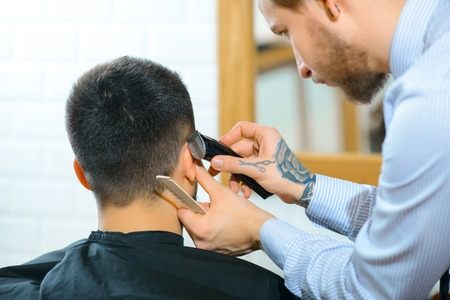 barbery: Best service for everyone. Pleasant professional barber holding razor and making haircut Stock Photo