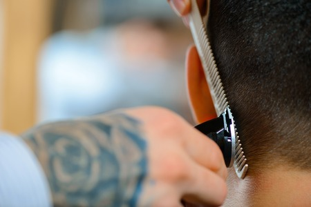 barbery: Crafty man. Close up of razor and comb in hands of professional barber holding them while making haircut