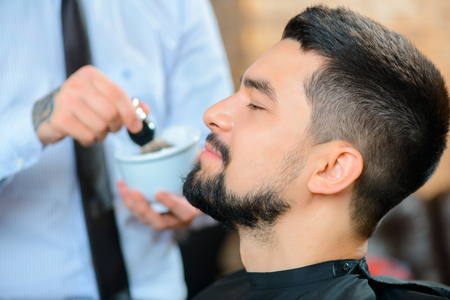 barbery: Stay handsome. Selective focus of pleasant content man sitting in the barber shop with professional barber standing in the background Stock Photo