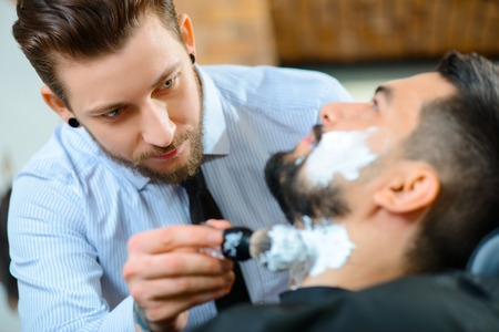 barbery: I do my job perfect. Selective focus of professional barber holding brush and applying foam on the face of his client while going to shave Stock Photo