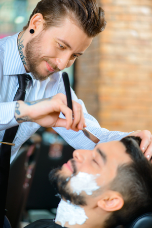 barbery: Like my job. Pleasant content smiling barber holding open razor while shaving beard of his client Stock Photo