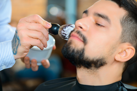 barbery: I will make you happy . Close up of brush in handsome professional barber applying shaving foam on the beard of his client