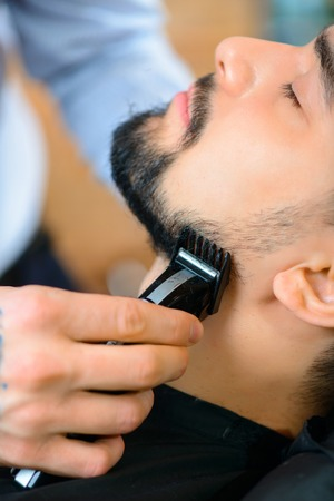 barbery: Take care of you beard. Close up of razor in hands of crafty professional hairdresser shaving his client