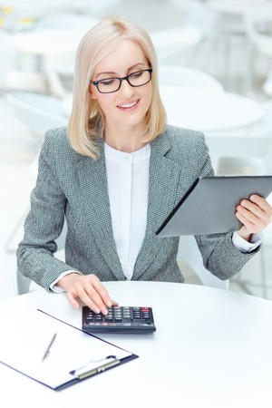 to be pleasant: Be accurate. Pleasant smiling professional businesswoman making calculation and sitting at the table while being involved in work