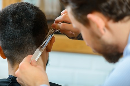 barbery: The best hair cut. Close up of scissors in hands of professional barber holding them and concentrating on work while making hair cut Stock Photo