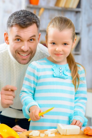 pleasant: Little chef. Pleasant little girl cutting cheese and making salad while cooking with her father Stock Photo