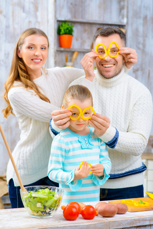 happy moment: Happy moment. Pleasant overjoyed family holding slices of pepper on their eye and cooking salad while having fun in the kitchen