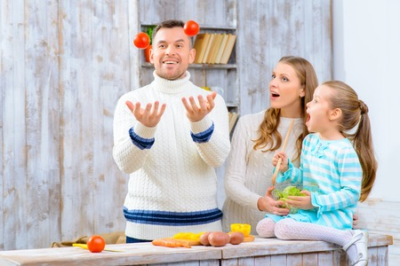 juggling: See  what I can. Pleasant loving father juggling the tomatoes and having fun with his family in the kitchen Stock Photo