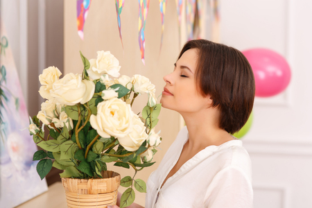 inhaling: Inhaling the scent. Young nice-looking lady is enjoying the flower scent Stock Photo