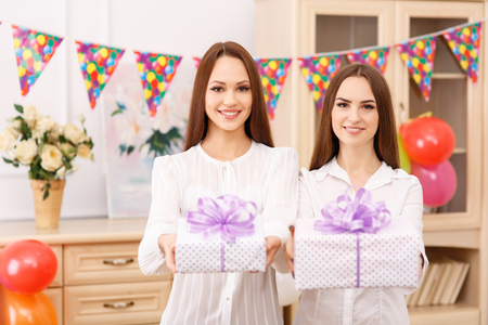 radiantly: Beautiful presents. Two attractive young girls are smiling radiantly while holding two present boxes. Stock Photo