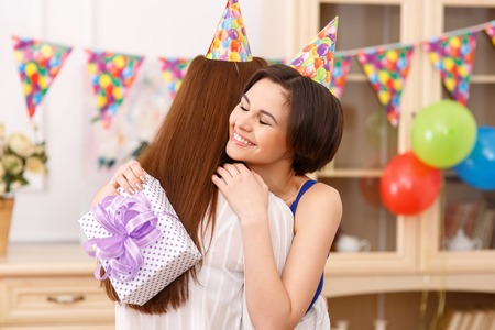 happy moment: Happy moment. Young nice-looking birthday girl is hugging her girl friend after receiving a present.