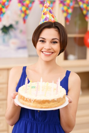 radiantly: Birthday cake. Young attractive girl is smiling radiantly while holding her birthday cake.