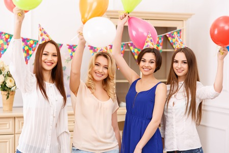 upholding: Party is on. Four attractive young girls are smiling cheerfully while upholding colorful balloons Stock Photo